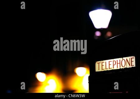 Red telephone box in Durham city at night - Stock Photo