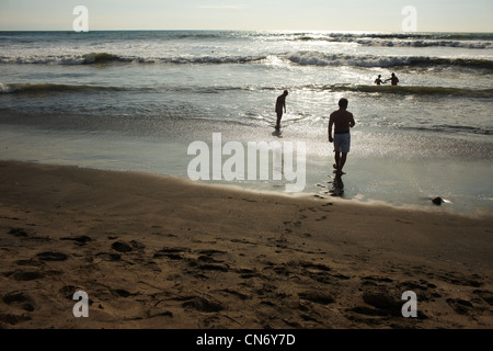 Pacific Beach, a couple of people bathing in the ocean, two people go swimming, water glitters sunset. - Stock Photo