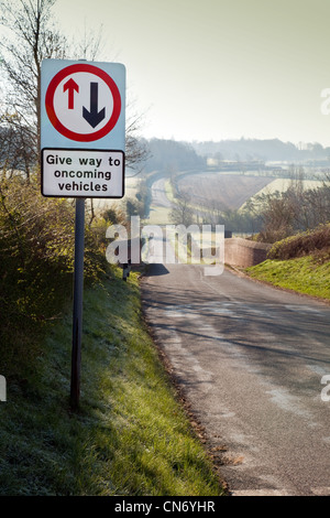 Give way sign at a humpback bridge on a country road in Cambridgeshire, East Anglia, UK - Stock Photo