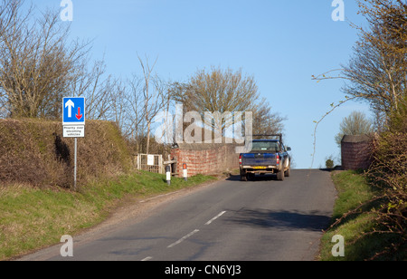 A car going over a humpback bridge on a country road cambridgeshire UK - Stock Photo