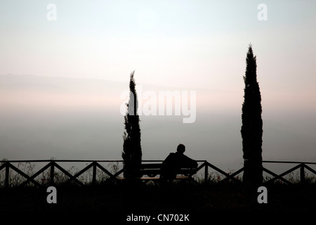A man watches the sunrise through the fog from the gardens of Saint Patricks Well in Orvieto, Italy - Stock Photo