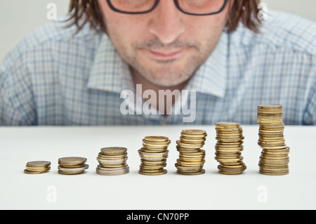 Businessman siting at the table and thinking about possible dollar invesments. - Stock Photo