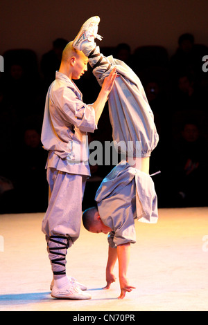 A Shaolin monk standing on his two fingers - Stock Photo