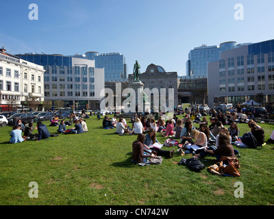 Many people enjoying the sun during their lunch break on the grass of the Place du Luxembourg in Brussels, Belgium - Stock Photo