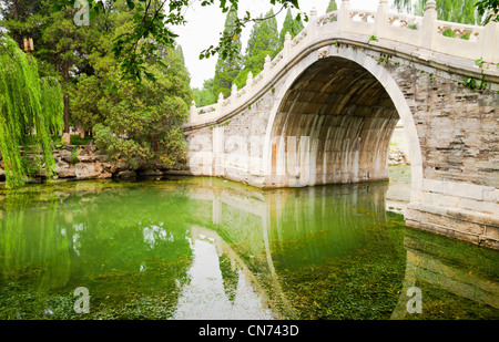 Old style stone Chinese arch bridge in a green garden pond in Beijing, China - Stock Photo