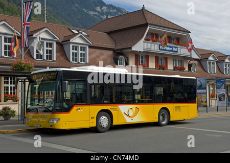 Post bus outside the Ost station in Interlaken in the Canton of Bern in Switzerland - Stock Photo