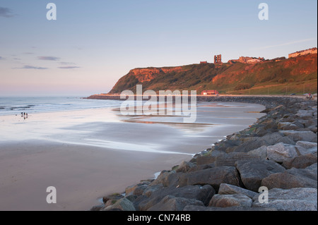 Picturesque view of blue evening sky, smooth, flat, sandy beach, calm sea & sunlit castle on cliff - North Bay, - Stock Photo