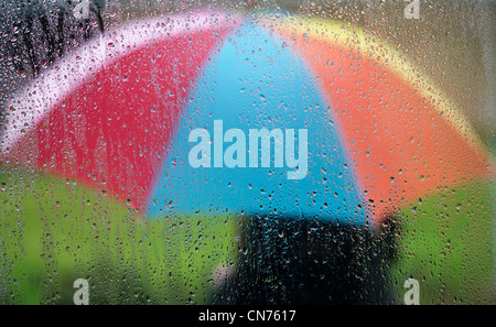 Raindrops on a window pane with a person holding a rainbow coloured umbrella outside - Stock Photo