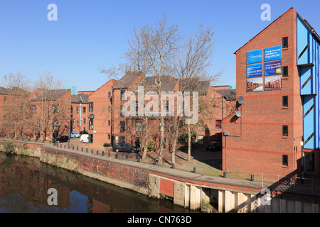New waterfront apartments advertised for sale on redeveloped wharf beside the River Aire in Leeds West Yorkshire - Stock Photo