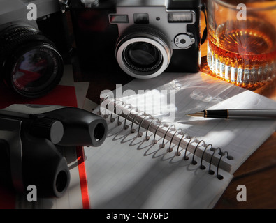 cameras, binoculars,  a liquor glass,  and an open journal and pen resting on a wooden table - Stock Photo
