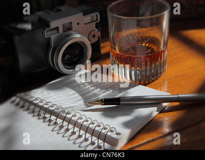 a pen resting on an open journal page, a camera and a liquor glass on a wooden table - Stock Photo