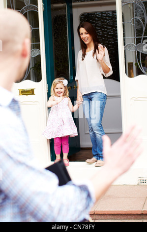 Mother and daughter waving to father - Stock Photo