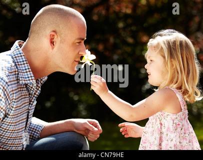 Girl holding flower for parent - Stock Photo