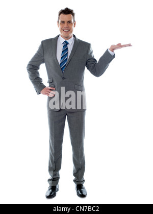 Portrait of a happy young businessman presenting a product against white background - copyspace - Stock Photo