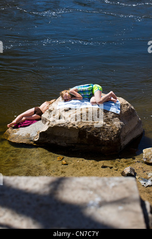 Two young girls sunbathing on a large boulder in the spring sun. Arkansas River, Salida, Colorado, USA - Stock Photo
