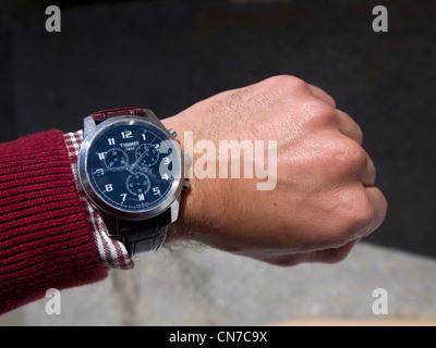 Person using a Tissot wristwatch - Stock Photo