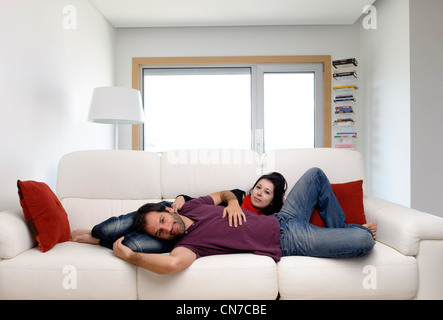 Young couple at home in the living room lying on a white sofa - Stock Photo