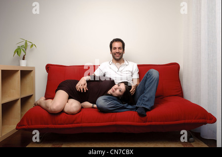 Happy young couple sitting on a sofa in the living room - Stock Photo
