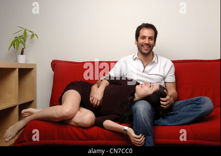 Happy young couple sitting on a red sofa in the living room - Stock Photo