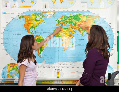11-13 year old interracial Hispanic girl presents geography lesson speech lecture front of classroom person people - Stock Photo