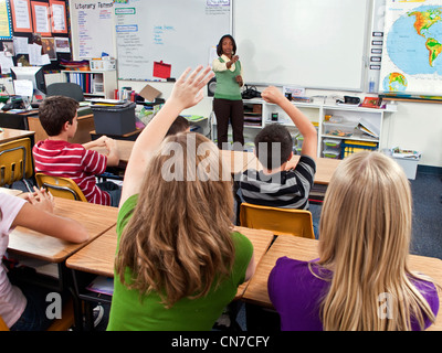 interracial inter multi ethnic racial diversity racially diverse multicultural cultural Students raise raising hands - Stock Photo