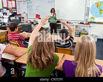 interracial inter multi ethnic racial diversity racially diverse multicultural cultural Students raise raising hands - Stock Photo