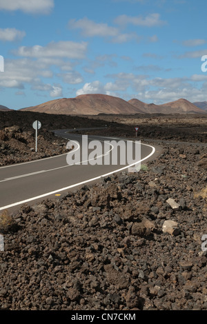 Road through the lava fields of Lanzarote in the Canary Islands with the volcanoes of Timanfaya in the background - Stock Photo