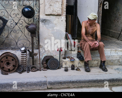 A middle-aged Cuban man sits on the front stoop of his house selling used auto parts in Havana, Cuba. - Stock Photo