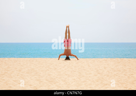 Man practicing yoga on beach - Stock Photo
