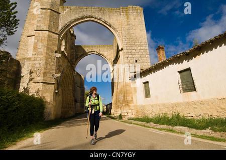 Spain, Castile and Leon, Castrojeriz, a stop on el Camino de Santiago, pilgrims walking below the arcades of San - Stock Photo