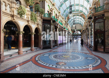 Floor mosaic and traditional upmarket designer shops in County Arcade in Victoria Quarter shopping centre in Leeds - Stock Photo