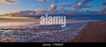 Panorama of autumn sunset and showers on tranquil deserted beach at low tide at Snettisham, Norfolk, UK - Stock Photo