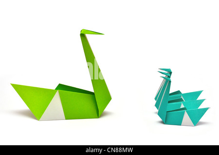 Origami Green and Blue Paper Swans meeting for a brief cut out white background Paper folding - Stock Photo