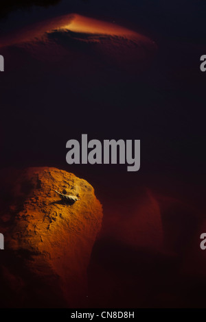 Submerged rocks and dry leaves in Rio Tinto - Stock Photo