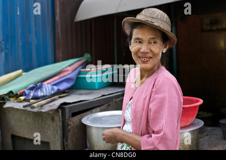 Street portrait of Burmese woman in traditional bamboo hat and wearing thanaka face cosmetic - Stock Photo