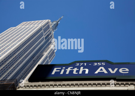 Fifth Avenue street sign with the Empire State Building in the background in Manhattan, New York City - Stock Photo