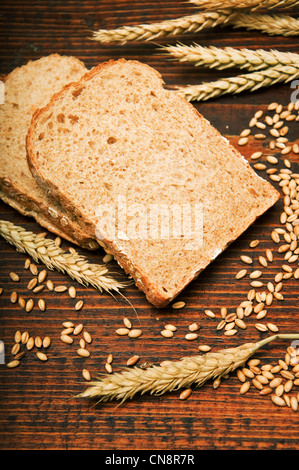 Wheat bread and grains and wheat ears on a wooden table - Stock Photo