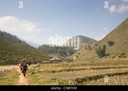 Black Hmong hill tribe girls walking on trail in Lao Chai village near Sapa town, Vietnam - Stock Photo