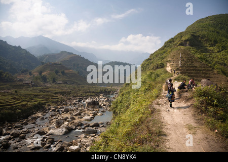 Black Hmong girls on a trail in Lao Chai village near Sapa town, Lao Cai Provence, Vietnam - Stock Photo