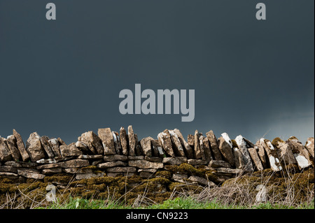 Stormy rain clouds over old dry stone wall in the English countryside - Stock Photo