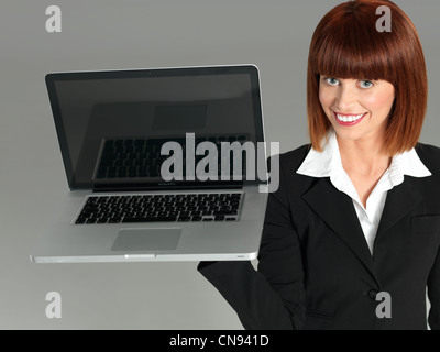 portrait of a beautiful, young businesswoman, holding an opened laptop, smiling, on gray background - Stock Photo