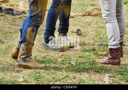 Cowgirls wearing muddy boots in a rodeo show. - Stock Photo