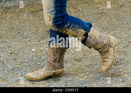 Cowgirl wearing muddy boots in a rodeo show. - Stock Photo