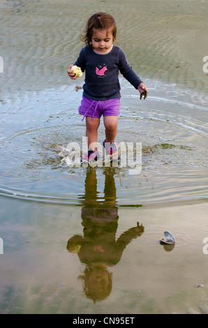 Little girl plays in a puddle of water. - Stock Photo