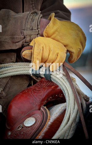Cowboy in saddle with yellow leather gloves - Stock Photo