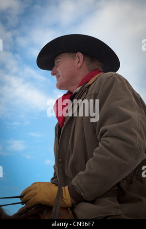 Cowboy in saddle with yellow leather gloves.  Captured on ranch in northeastern Wyoming. - Stock Photo