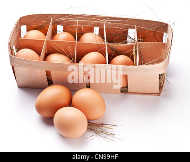 Eggs with a straw in a wooden basket on a white background. - Stock Photo