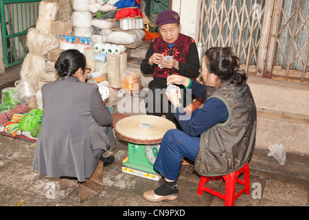 Three women stallholders playing cards on a pavement in the old town, Hanoi, Vietnam - Stock Photo