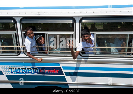 Shir Lankan School boys wave from a bus window in Galle Fort Sri Lanka - Stock Photo