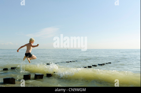 Boy jumping on posts in ocean - Stock Photo